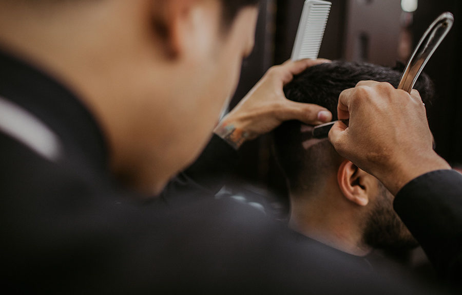 Barber giving man haircut and shaving with blade and comb