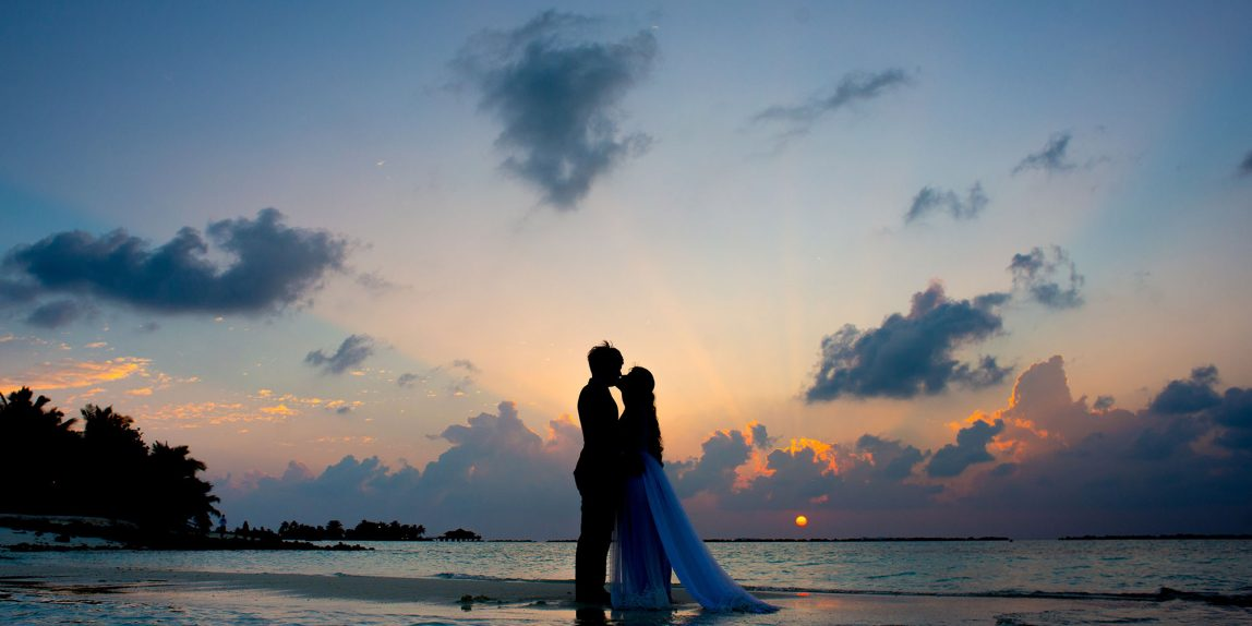 couple wearing wedding attire standing on beach at sunset